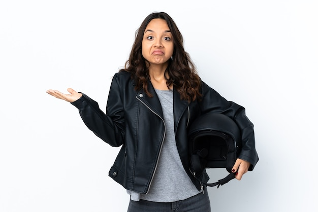 Young woman holding a motorcycle helmet over isolated white wall having doubts while raising hands