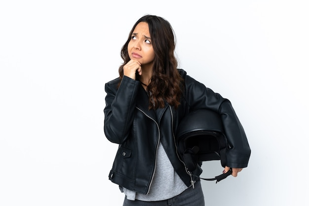 Young woman holding a motorcycle helmet over isolated white wall having doubts and with confuse face expression