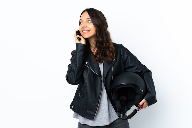 Young woman holding a motorcycle helmet over isolated white wall keeping a conversation with the mobile phone with someone