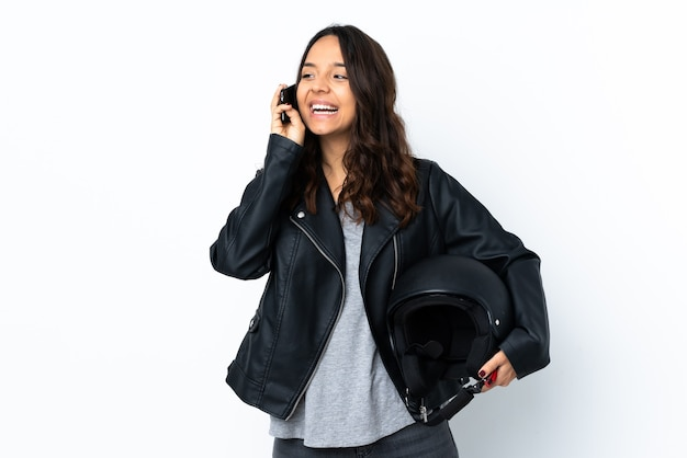 Young woman holding a motorcycle helmet over isolated white wall keeping a conversation with the mobile phone