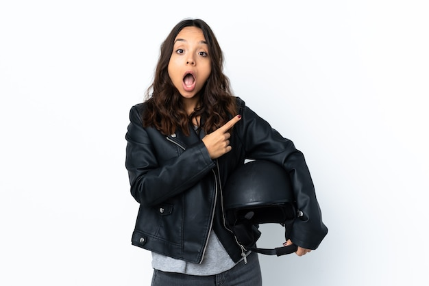 Young woman holding a motorcycle helmet over isolated white wall surprised and pointing side