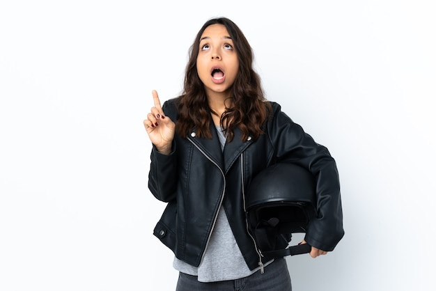 Young woman holding a motorcycle helmet over isolated white wall surprised and pointing up