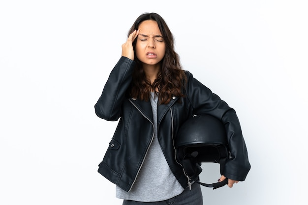Young woman holding a motorcycle helmet over isolated white with headache