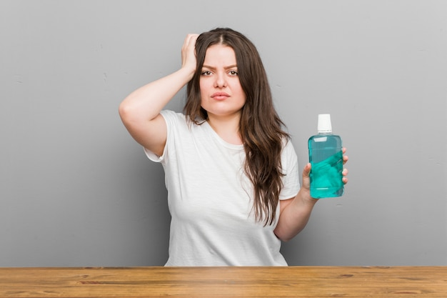 Young woman holding a mouthwash being shocked,