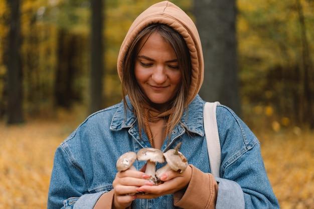 森の中でキノコを保持している若い女性。