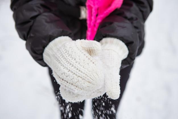 눈덩이, 숲, 야외에서 겨울 날을 만들기 위해 그녀의 손에 자연 부드러운 하얀 눈을 들고 젊은 여자. 확대.