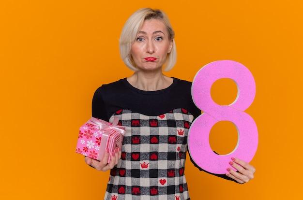 段ボールとプレゼントで作られた8番を保持している若い女性