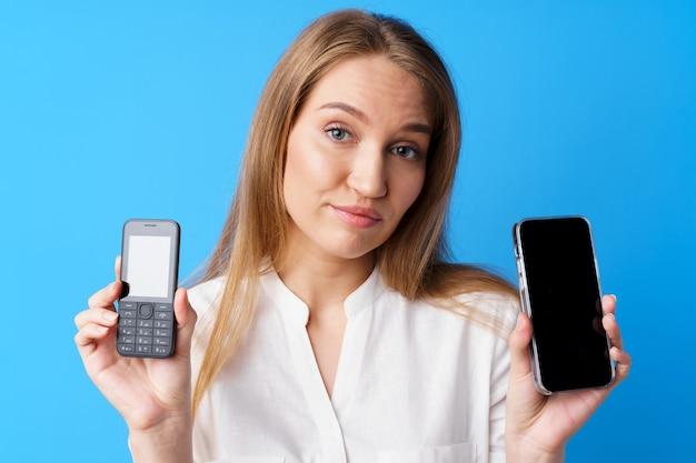 파란색 배경에 대해 오래된 전화기와 새 전화기를 들고 있는 젊은 여성