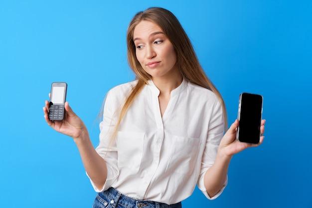 Молодая женщина, держащая старый и новый телефон на синем фоне