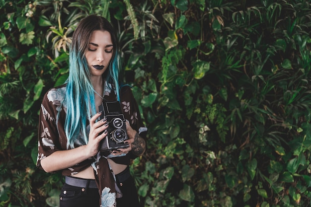 오래 된 레트로 스타일의 카메라를 손에 들고 젊은 여자