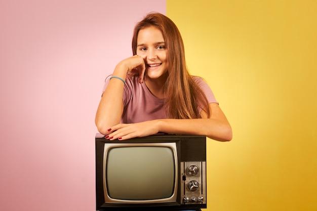 Молодая женщина, держащая старый ретро-телевизор, сидя на желтом и розовом фоне