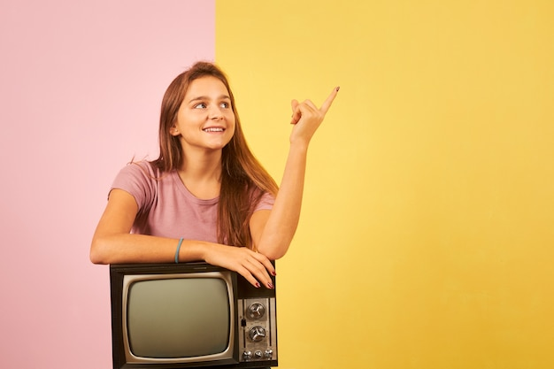 Young woman holding old retro tv sitting against yellow and pink background pointing with finger to the side