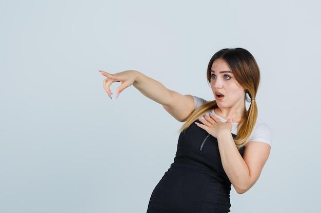 Giovane donna che tiene una mano sul petto mentre indica via e sembra sorpresa