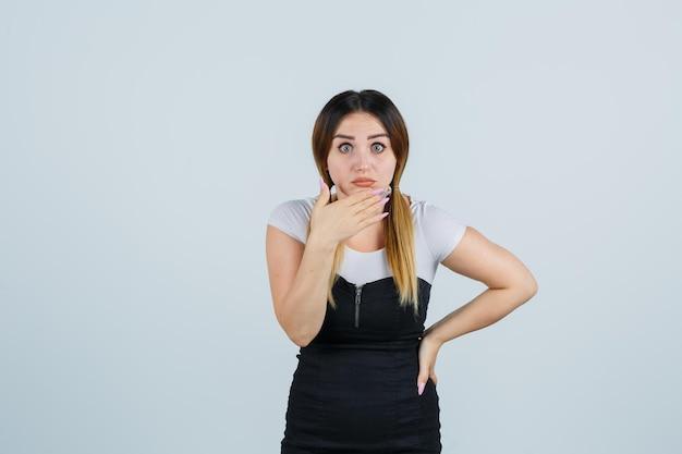Giovane donna che tiene una mano sul mento e sembra scioccata