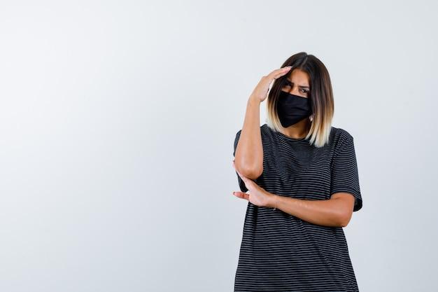 Giovane donna che tiene una mano sulla fronte, un'altra mano sotto il gomito in abito nero, maschera nera e sembra seria, vista frontale.