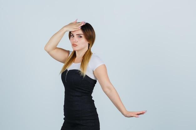 Giovane donna che tiene una mano sulla fronte e sembra tormentata