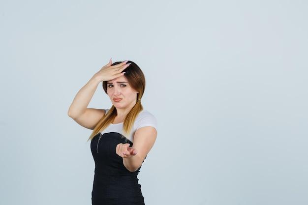 Giovane donna che tiene una mano sulla fronte mentre indica con il dito indice e sembra delusa