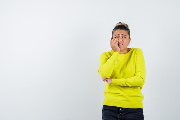 Молодая женщина, держащая одну руку возле рта, а другую руку на локте в желтом свитере и черных брюках, выглядит взволнованной