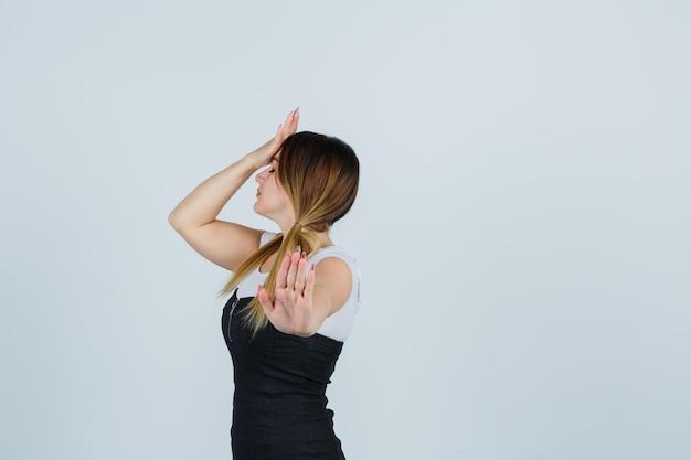 一時停止の標識を表示しながら額に片手を保持している若い女性