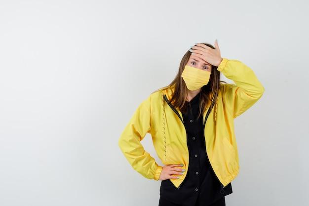 額に片手を持っている若い女性