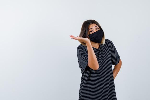 Giovane donna che tiene una mano sulla vita, allargando un'altra mano da parte in abito nero, maschera nera e sembra carina. vista frontale.