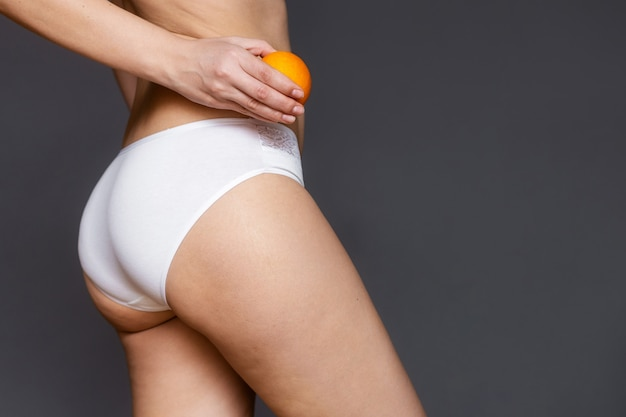 Young woman holding an orange on a light wall. cellulite problem concept