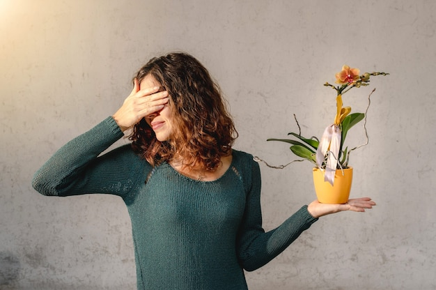 난초 식물을 들고 젊은 여자는 손으로 그녀의 눈을 커버.