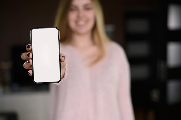 彼女の手で携帯電話を持って、モックアップ、スペースをコピーする若い女性。高品質の写真