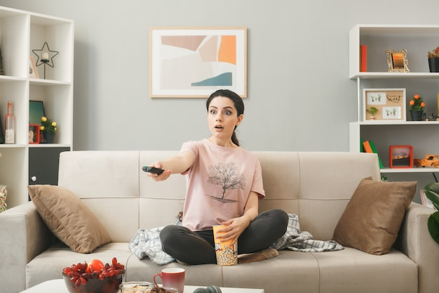 Young woman holding out tv remote to camera sitting on sofa behind coffee table in living room