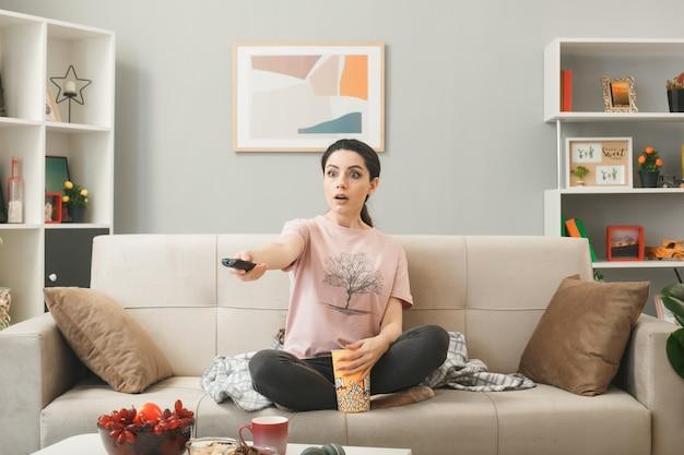 Молодая женщина, протягивая пульт от телевизора к камере, сидит на диване за журнальным столиком в гостиной