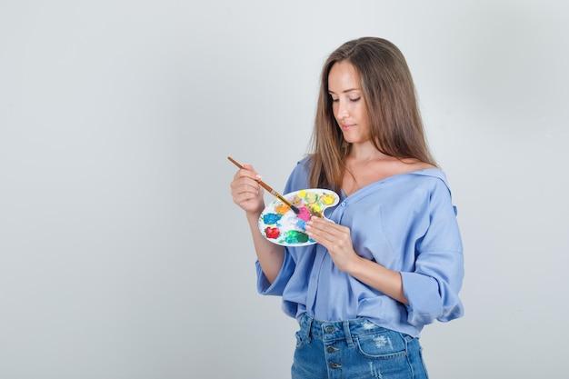 Giovane donna che tiene il pennello sulla tavolozza in camicia