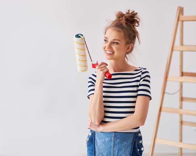 Young woman holding a paint roller