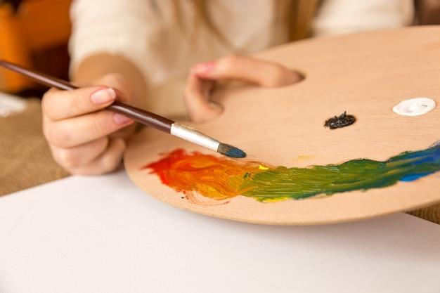 Молодая женщина держит кисть и выбирает краску на поддоне