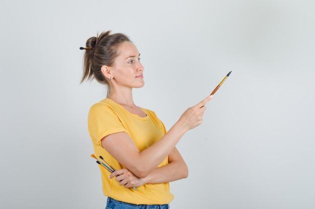 Молодая женщина держит инструменты для рисования и смотрит в желтую футболку