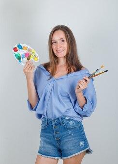 Молодая женщина держит инструменты для рисования в синей рубашке, шортах и выглядит веселой