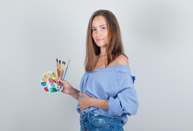 Молодая женщина, держащая инструменты для рисования в голубой рубашке, шортах и уверенно выглядящая.