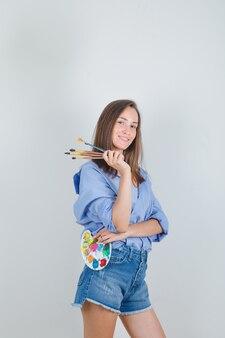 Молодая женщина, держащая инструменты для рисования в голубой рубашке, шортах и выглядящая счастливой.