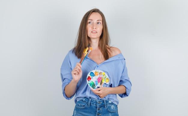 Молодая женщина держит инструменты для рисования в синей рубашке, шортах и выглядит обнадеживающей