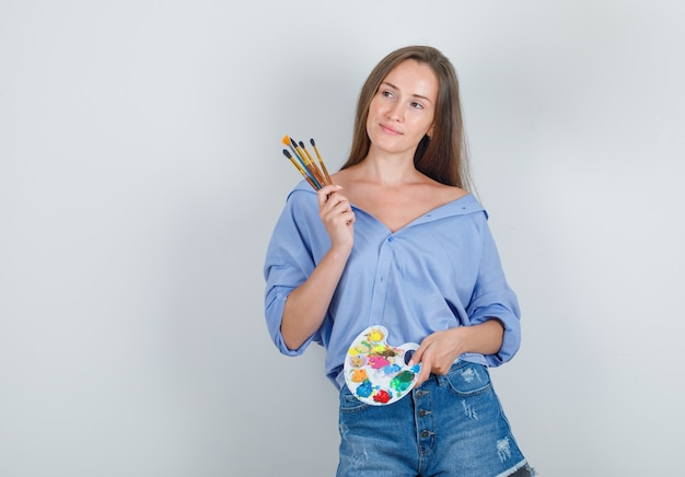 Молодая женщина держит инструменты для рисования в рубашке, шортах и радуется