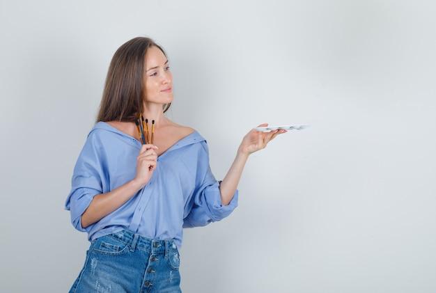 Молодая женщина держит инструменты для рисования в рубашке, шортах и выглядит весело