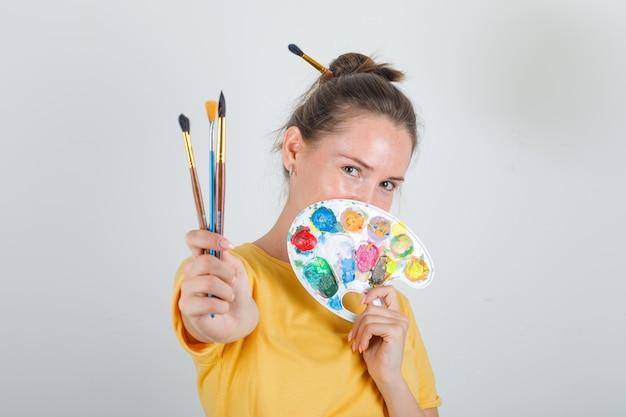 Молодая женщина держит инструменты для рисования в желтой футболке и выглядит счастливой