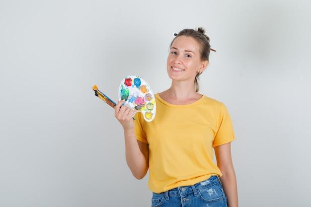 Молодая женщина, держащая инструменты для рисования в желтой футболке, джинсовых шортах и веселый вид.