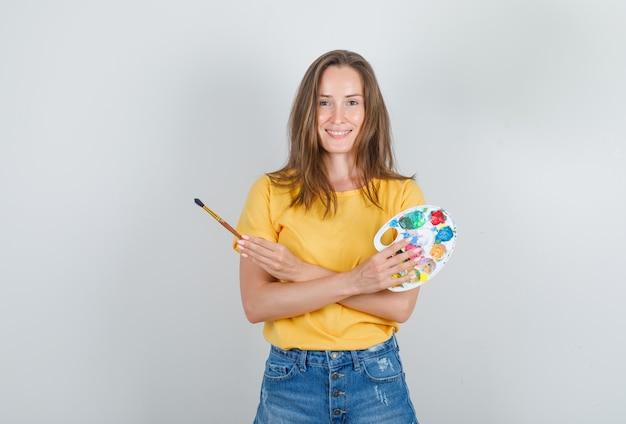 Молодая женщина держит инструменты для рисования в желтой футболке, джинсовых шортах и выглядит весело