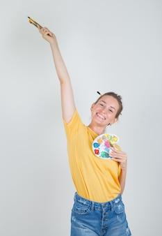 Молодая женщина держит инструменты для рисования в желтой футболке, джинсовых шортах и выглядит энергичной
