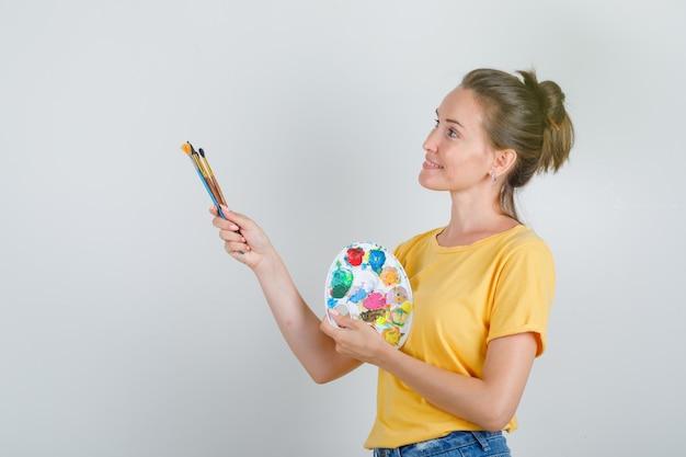 Молодая женщина, держащая инструменты для рисования, глядя вверх в желтой футболке, джинсовых шортах и выглядит веселой.