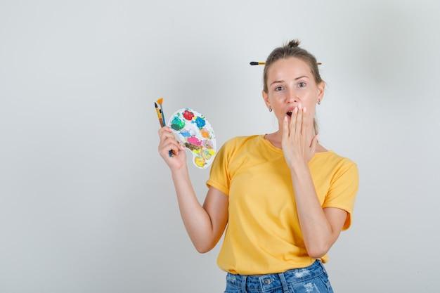 Giovane donna che tiene gli strumenti di pittura con la mano sulla bocca in maglietta gialla, pantaloncini di jeans e guardando sorpreso