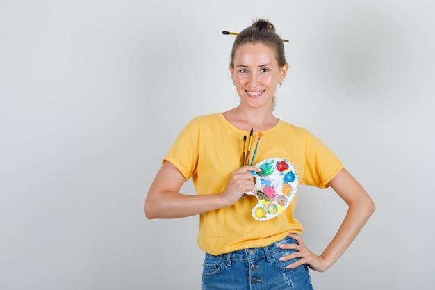 Giovane donna che tiene gli strumenti di pittura con la mano sulla vita in maglietta gialla, pantaloncini di jeans e sembra allegro