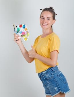 Молодая женщина держит инструменты для рисования с большим пальцем вверх в желтой футболке, джинсовых шортах и выглядит веселой