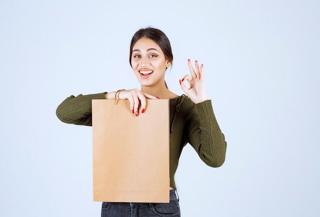 Giovane donna che tiene un sacco di carta e che dà segno giusto su fondo bianco.