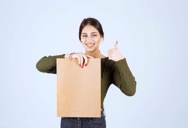 Giovane donna che tiene un sacco di carta e che dà i pollici in su su priorità bassa bianca.